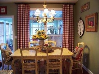 Loc pentru luat masa amenajat in stil rustic cu draperii in carouri alb cu rosu