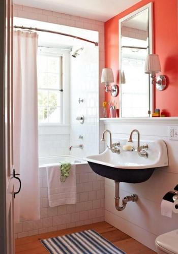 Baie retro alba cu chiuveta din fonta si peretele cu oglinda zugravit in portocaliu