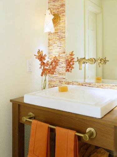Baie zugravita cu crem si un perete cu mozaic dreptunghiular cu joc de diferite nuante de portocaliu