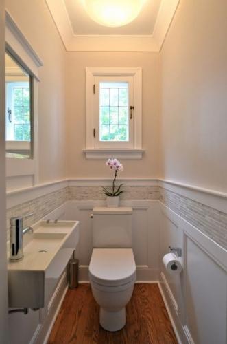 Baie cu chiuveta ingusta pereti si obiecte sanitare albe si brau decorativ crem din mozaic