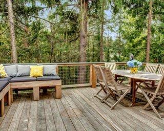 Terasa de lemn cu canapea cu pernute colorate