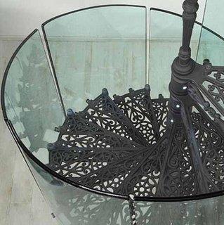 Scara interioara in spirala cu trepte din fier forjat si balustrada din sticla