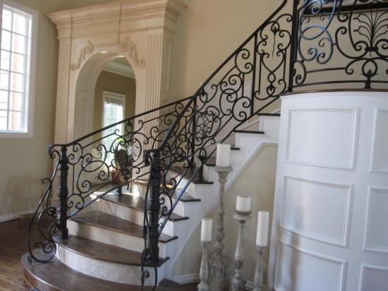 Scara interioara placata cu marmura si balustrada din fier si lemn