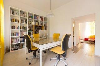 Zona de birou cu masa mare si scaune colorate si biblioteca mare pe perete