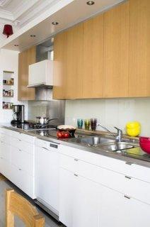 Bucatarie de apartament cu corpuri albe de mobilier la baza si corpuri suspendate din lemn