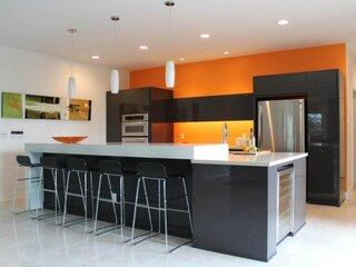 Mobila bucatarie neagra cu blat alb si pereti portocalii