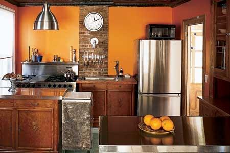 Bucatarie cu zugraveala portocalie si perete placat partial ci caramida