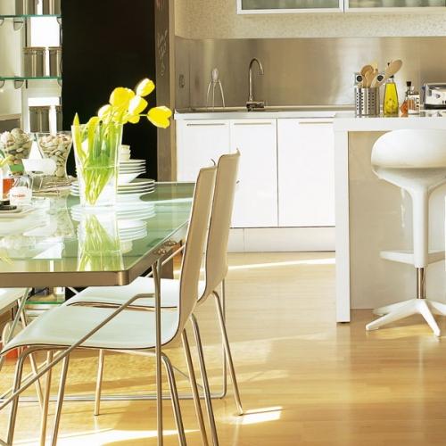 Locul pentru luat masa cu masa din sticla  amplasat langa zona de living