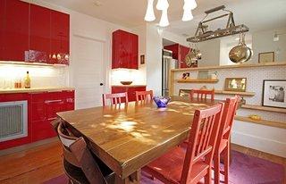 Bucatarie cu corpuri rosii lucioase si masa din lemn masiv cu scaune rosii