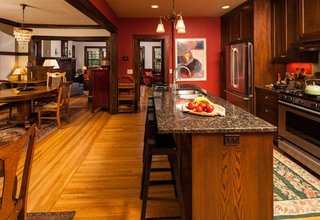 Bucatarie open space cu mobila clasica din lemn si peretii rosii