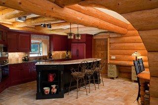 Bucatarie rustica cu pereti placati cu busteni si mobila rosie
