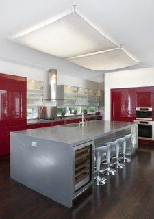 Insula de bucatarie argintie si mobila rosie lucioasa