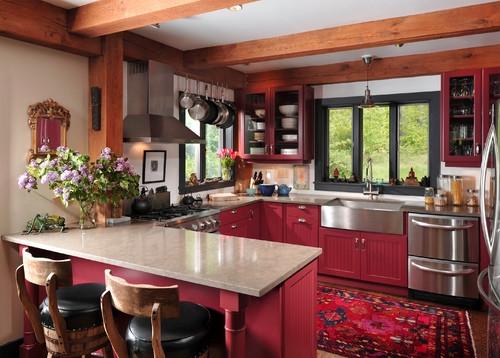 Mobila rosie de bucatarie pe toate laturile si tavan alb cu barne de lemn