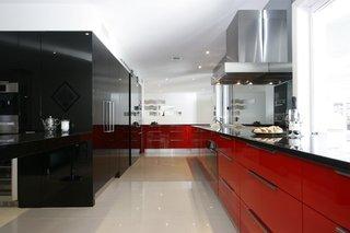 Mobila rosie pe un perete si neagra pe celalalt intr-o bucatarie moderna
