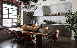 Dining si bucatarie amenajate in stil industrial cu perete de caramida alba