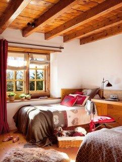 Dormitor cu doua paturi asezate in colturile camerei