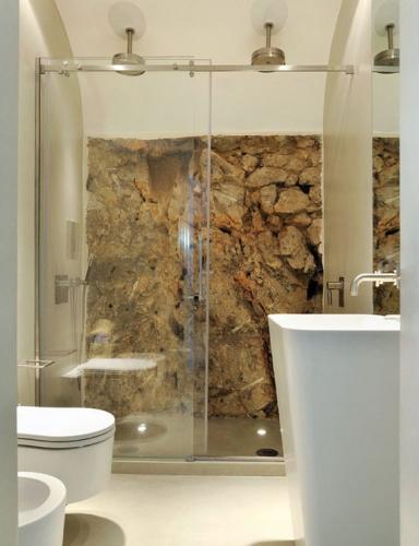 Cabina de dus cu perete din piatra si usa din sticla transparenta