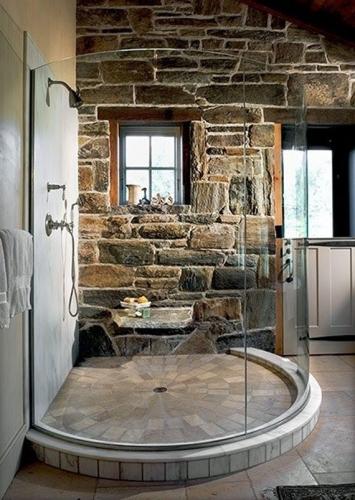 Cabina de dus rotunda din sticla in baie placata cu piatra de rau