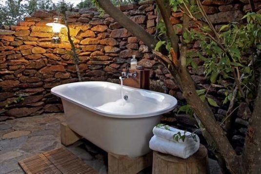 Cada de baie asezata pe doua bucati de lemn pe terasa