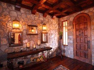 Hol de intrare placat cu piatra pe pereti si parchet din lemn masiv