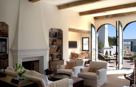 Living amenajat in stil colonial spaniolcu peretii albi si grinzi de lemn pe tavan