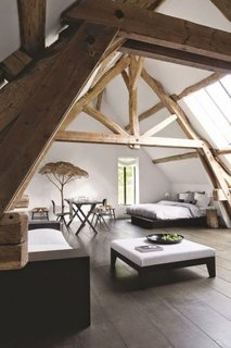 Dormitor rustic in mansarda decorat cu grinzi groase de lemn