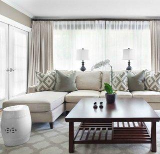 Coltar modular alb cu perne gri si cu modele geometrice asortate cu covorul