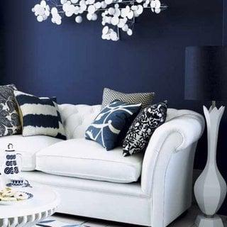 Perete de accent albastru inchis si canapea din piele alba