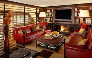 Living amenajat cu doua canapele din piele rosie si perne decorative