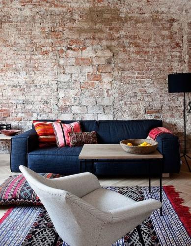 Atmosfera moderna rustica cu perete de caramida si perne puternic colorate