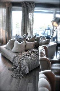 Canapea spatioasa accesorizata cu pernite chic si iluminator industrial