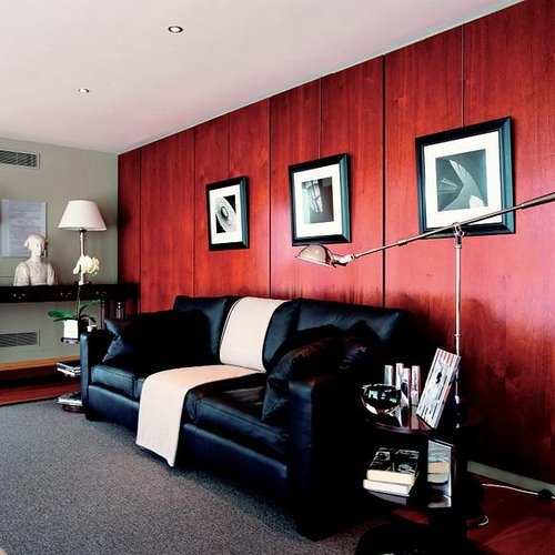 Canapea neagra din piele in living cu perete maro roscat