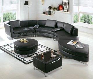 Canapea pe curb din piele neagra intr-un living monocromatic