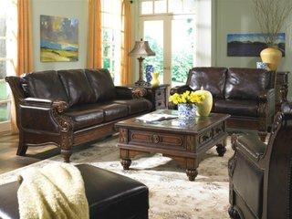 Living mobilat clasic cu canapea si fotolii din piele de culoare inchisa