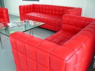 living mobilat cu canapea si fotolii din piele rosie