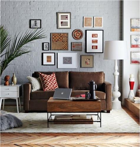 Canapea din piele inchisa la culoare si masuta de cafea cu blat din lemn si picioare din fier forjat