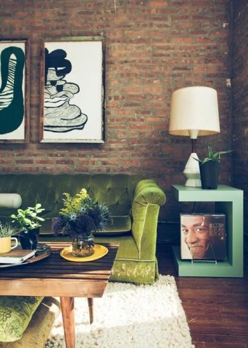Canapea din catifea verde si perete din caramida rosie
