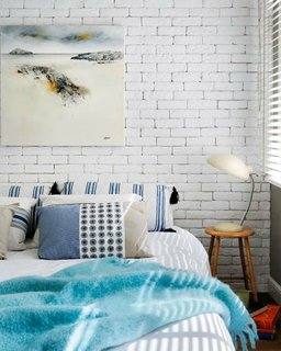 Dormitor in stil scandinav cu perete cu caramida vopsita
