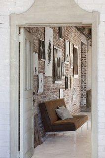 Hol cu perete de caramida si colectie de tablouri
