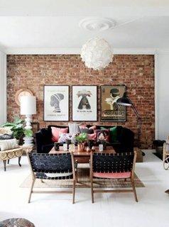Living cu perete de accent cu caramida, scaune si canapea neagra cu perne decorative roz