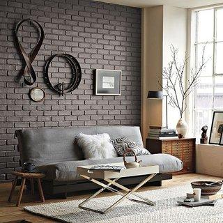 Living cu perete de accent din caramida vopsita cu gri