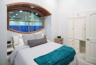 Dormitor mic cu pat asezat sub fereastra