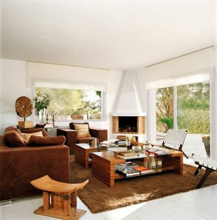 Zona de relaxare in living cu canapea in nuanta ocru si fotolii din piele alba impletita