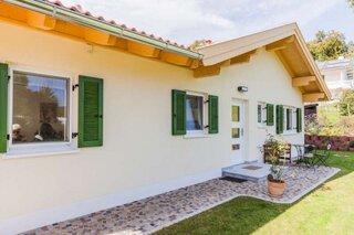 Casa micuta cu parter cu fatada alba si obloane din lemn de culoare verde