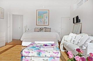 Dormitor cu pat pe mijloc si canapea alba cu trei locuri