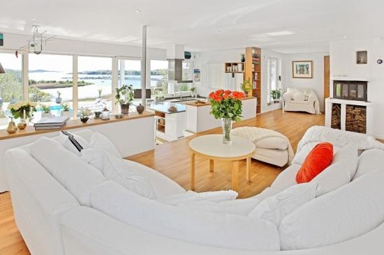Casa in stil nordic cu parchet din lemn masiv , mobila alba si ferestre supradimensionate.