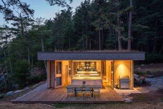 Casa de vacanta din lemn cu acoperis plat vedere exterioara pe timp de noapte