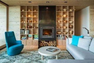 Living modern cu pereti din lemn si semineu flancat de rafturi