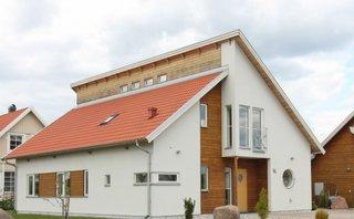 Casa moderna cu acoperis rosu si fatada alba cu lemn