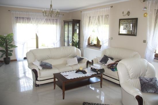Living cu gresie si canapele albe din piele